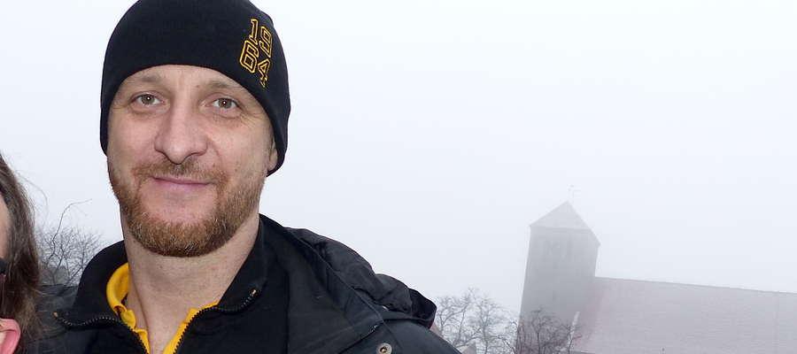 Piotr Gruszka, a w tle lubawski kościół Św. Anny