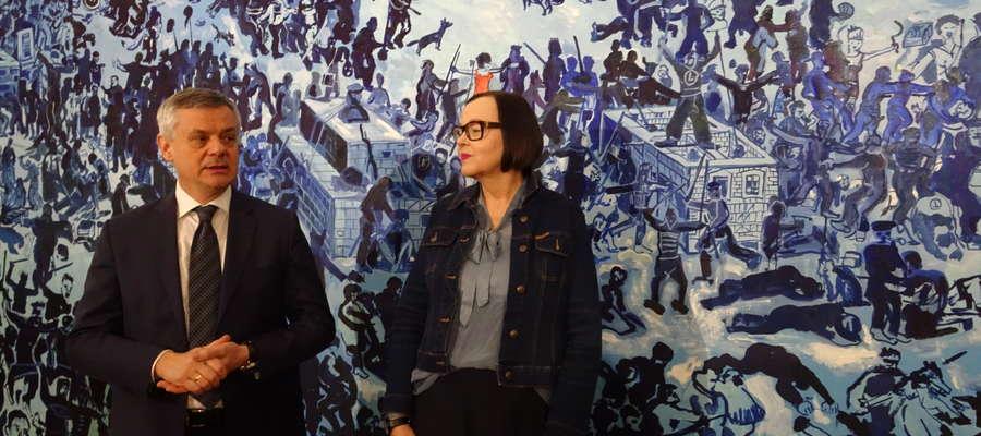 Piotr Żuchowski, dyrektor Muzeum Warmii i Mazur oraz kustosz Grażyna Prusińska  na tle Bitwy pod Grunwaldem Edwarda Dwurnika