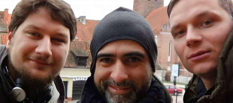 Piotr Splin i Abelard Giza w towarzystwie organizatora, Kamila Jankiewicza na tle reszelskiego zamku.