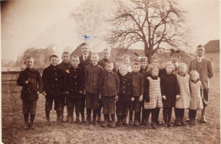 Pierwsi uczniowie szkoły w Pluskach (1930) ze swoim nauczycielem Robertem Gransickim. Na zdjęciu jest pięcioro dzieci z rodziny Popławskich.