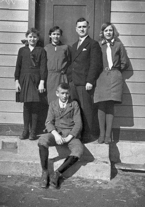Na schodach siedzi Izydor Poplawski, w tyle stoi nauczyciel – Robert Gransicki.