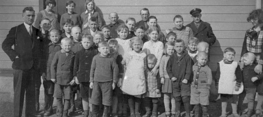 Dzieci ze szkoły w Pluskach. Wśród nich pięcioro z rodziny Popławskich. Dziewczynki po środku w białych sukienkach to Leokadia, Waleska i Adela Popławskie.