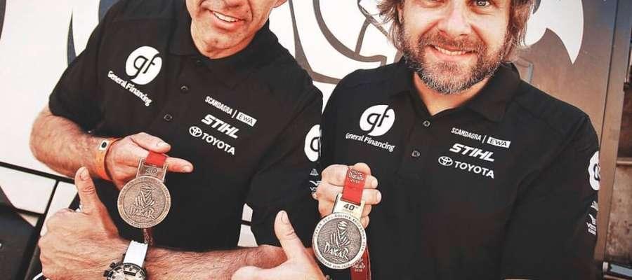 Sebastian Rozwadowski (z lewej) i Benediktas Vanagas prezentują pamiątkowe medale przyznane za ukończenie 40. Rajdu Dakar