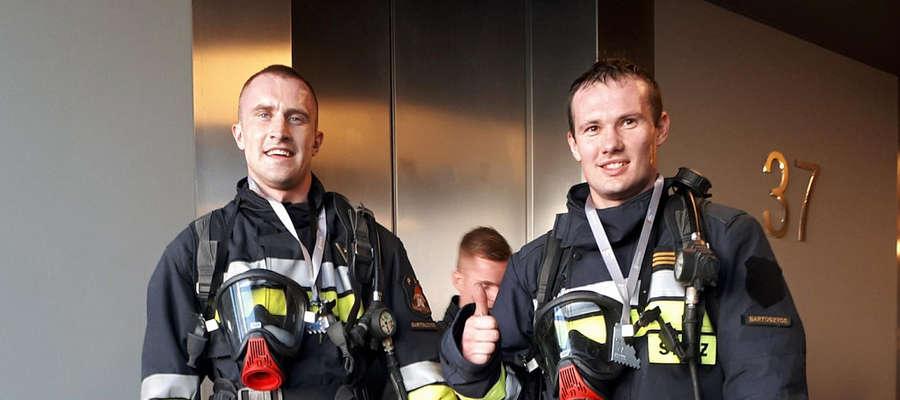 """Mł. asp. Zbigniew Rogowski (po lewej) i st. sekc. Marcin Wójcik po zakończeniu """"Strażackich schodów"""", na 37 piętrze biurowca Rondo 1 w Warszawie."""