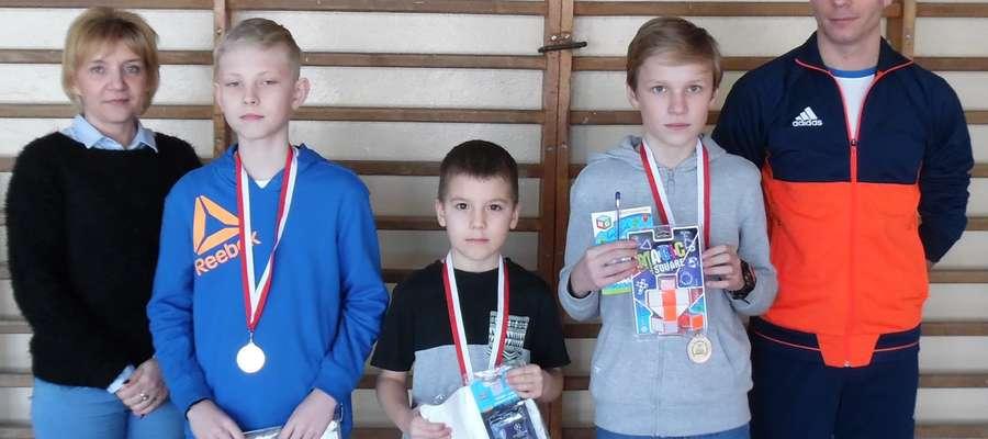 Najlepsi uczniowie w konkursie szachowym z dyrektorką szkoły i nauczycielem wychowania fizycznego