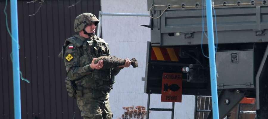 Żołnierz z jednostki w Braniewie przenosi niewybuch do specjalnego samochodu.