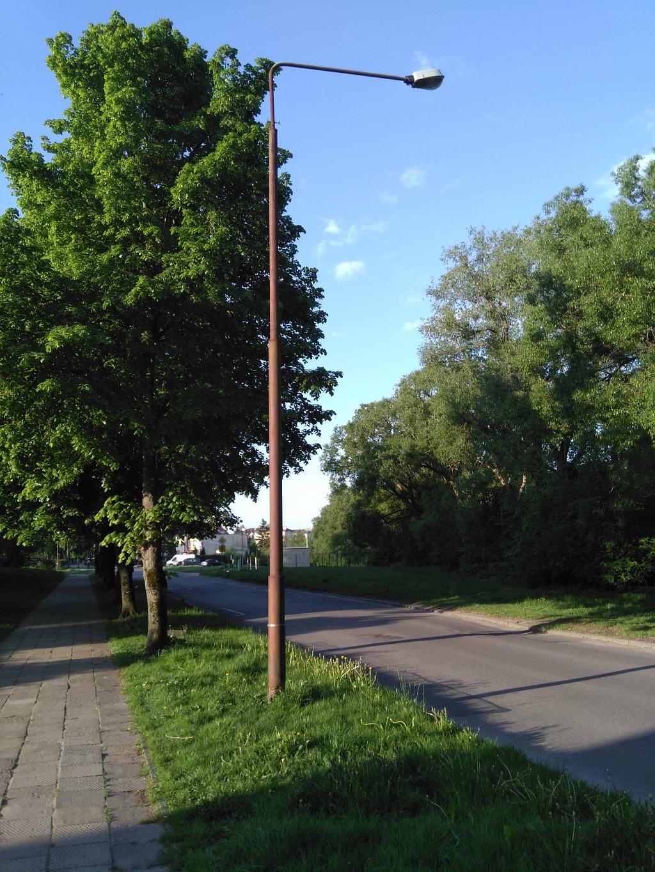 Lampa uliczna przy ul. Paderewskiego w Bartoszycach. Jej podstawa jest skorodowana.