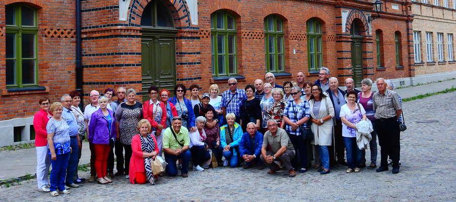Wycieczka członków PZERiI z różnych miejscowości powiatu nowomiejskiego pod typową budowlą fabrycznej Łodzi