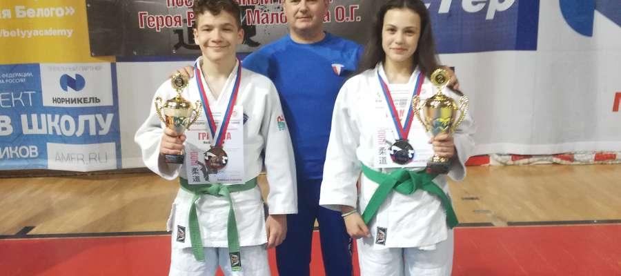 Trener Andrzej Grudziński oraz Jakub Kolos i Gabriela Czyżewska z Gwardii Olsztyn prezentują trofea wywalczone w Rosji