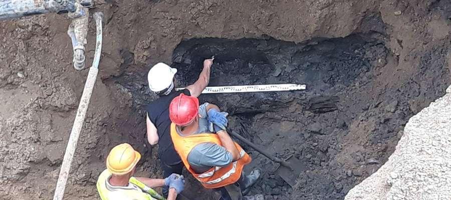 Izabela Mellin-Wyczółkowska prowadzi pomiary w wykopie na bartoszyckim deptaku.