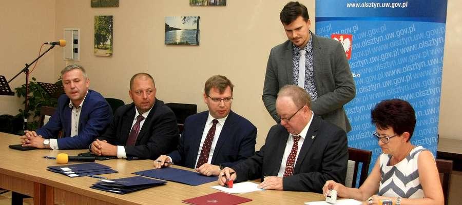 Wójt Jarosław Kuczyński i skarbnik gminy Wiesława Dowejko podpisują umowę z wojewodą Arturem Chojeckim