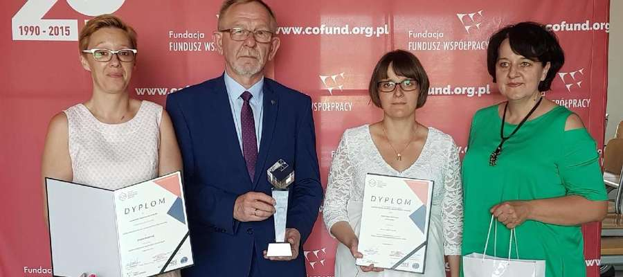 Dyrektor i nauczycielki podczas gali w Warszawie prezentują statuetkę i dyplomy
