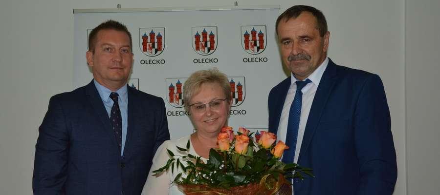 Burmistrz Wacław Olszewski (z prawej) i przewodniczący Rady Miejskiej w Olecku Wojciech Rejterada podziękowali Elżbiecie Rękawek za wieloletnią współpracę i kierowanie wydziałem edukacji