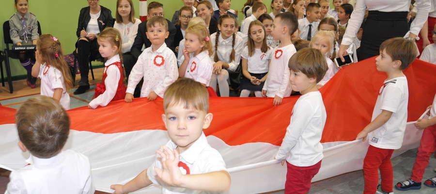 Przedszkolaki w biało - czerwonych strojach nieśli  trzydziestometrową flagą narodową