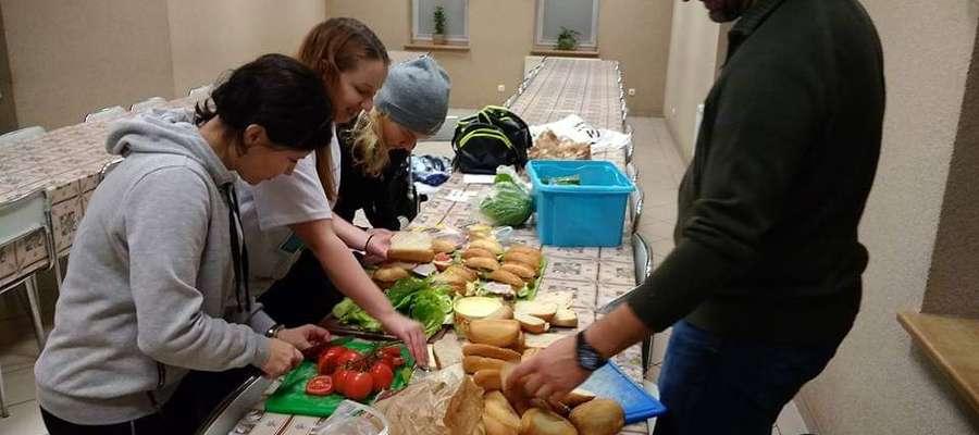 Wolontariusze podczas przygotowywania kanapek, którymi częstują potrzebujących na dworcu