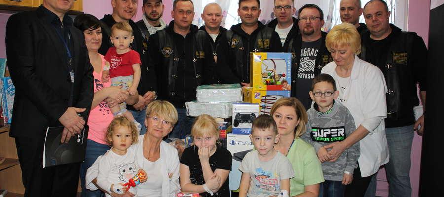 Członkowie klubu Moto Ósemka wraz z personelem oddziału dziecięcego, ordynator oddziału i dyrektorem szpitala oraz małymi pacjentami w sali zabaw