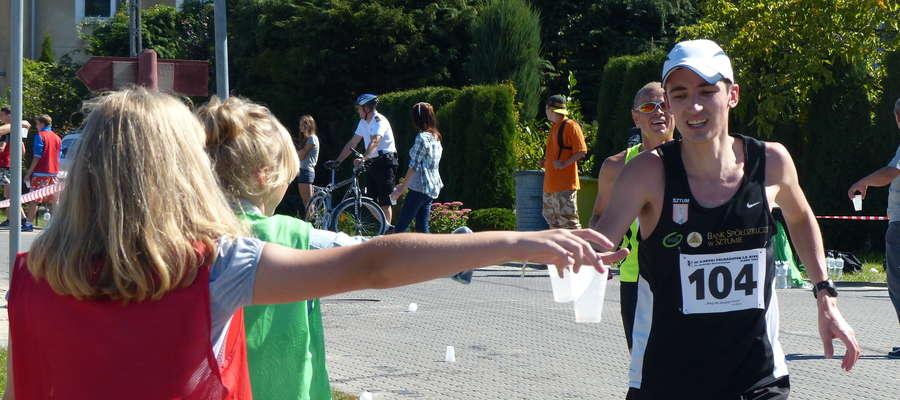 Zdjęcie ilustracyjne — III Iławski Półmaraton, biegacze korzystają z punkty z wodą i napojami izotonicznymi na Lipowym Dworze