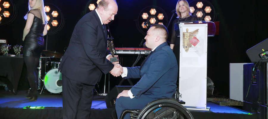 Aleksander Socha wręcza nagrodę Dawidowi Ostaszowi