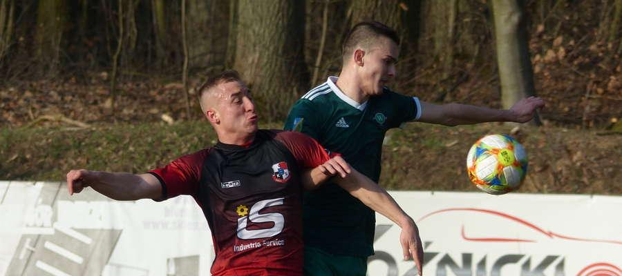Michał Jankowski (GKS Wikielec, zielona koszulka) walczy o piłkę z obrońcą zespołu z Giżycka