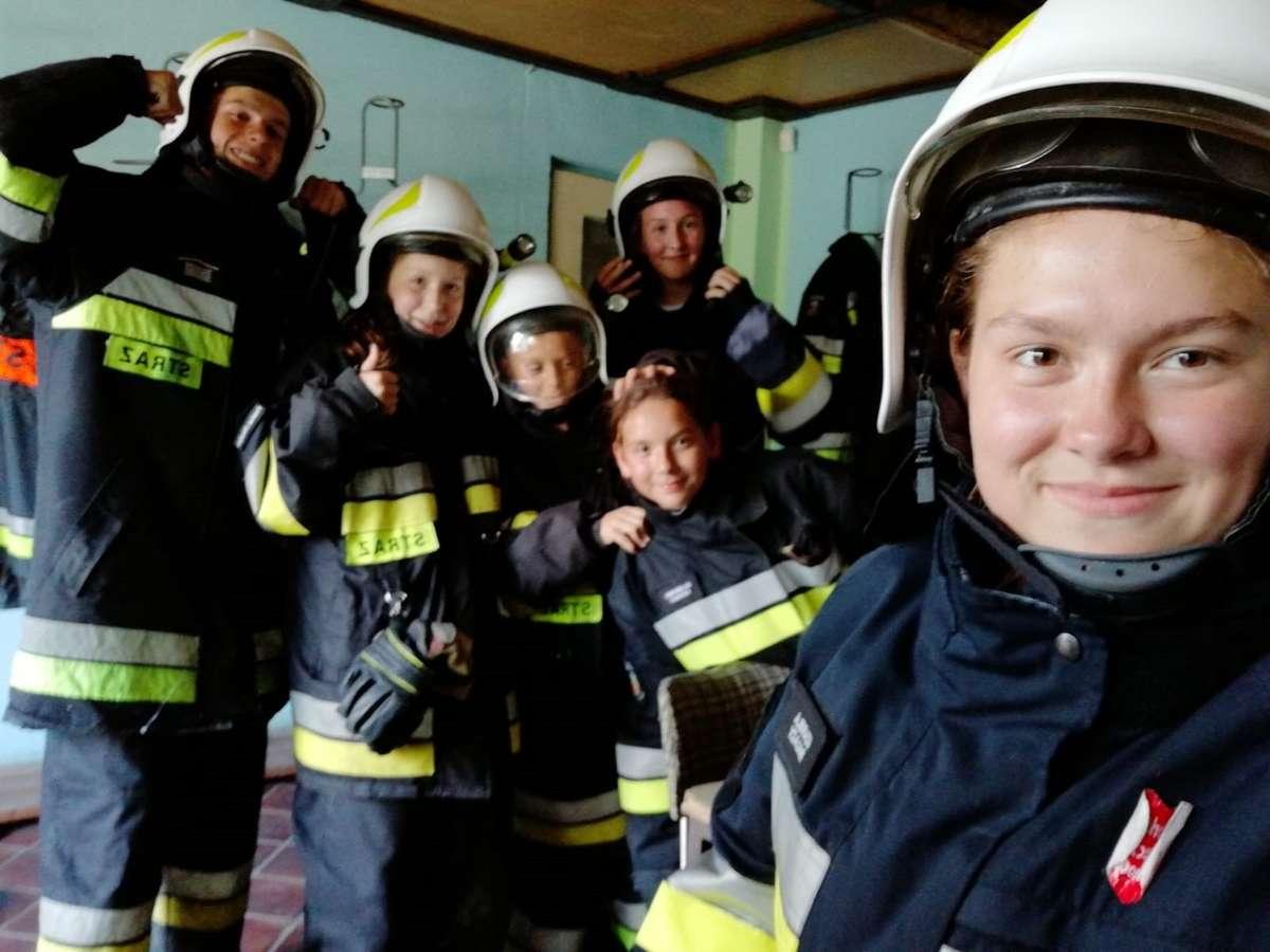 Modzi strażacy w strojach bojowych
