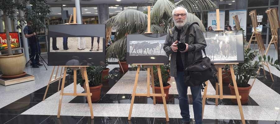 Piotr Dzięciołowski przy swoich pracach w holu Biblioteki Uniwersyteckiej UWM