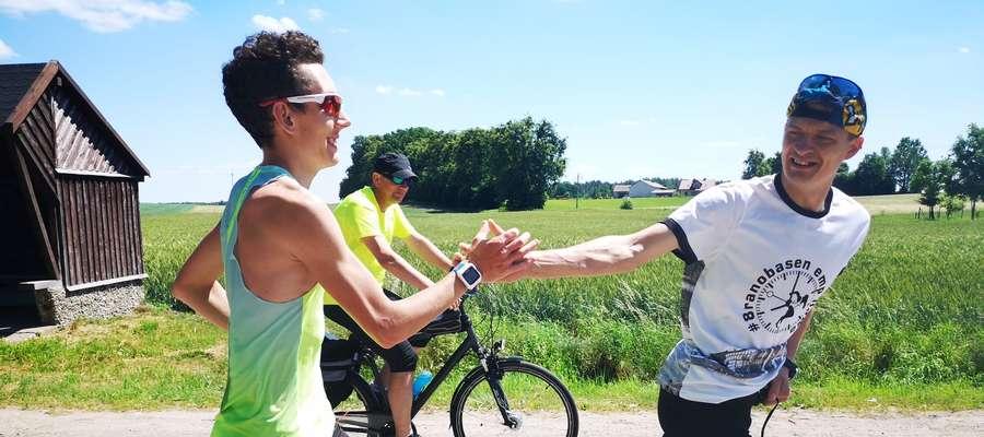 Zdjęcie-symbol. Michał Kołecki (z lewej) na trasie sztafety wokół Jezioraka przybija piątkę innemu biegaczowi z Iławy, Tomaszowi Klinickiemu