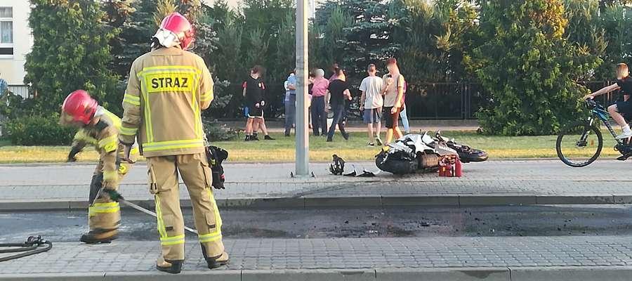 Już po akcji. Strażacy sprzątają miejsce, w którym płonął motocykl marki suzuki