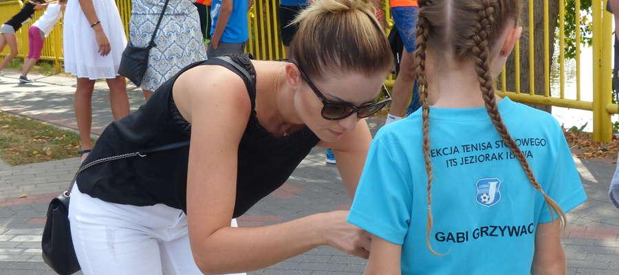 Mama Gabrieli Grzywacz (młoda tenisistka stołowa Jezioraka Iława) przypina jej numer startowy na VIII Iławskim Półmaratonie (2018 r). W Iławie dyscypliny i ich reprezentanci bardzo często przenikają się