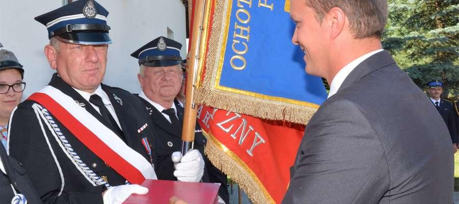 Komendant Wiesław Świtaj odbiera gratulacje od Macieja Nowika, przewodniczącego Rady Gminy w Świętajnie