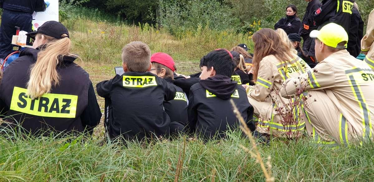 Dzieciaki słuchają wykładu w terenie
