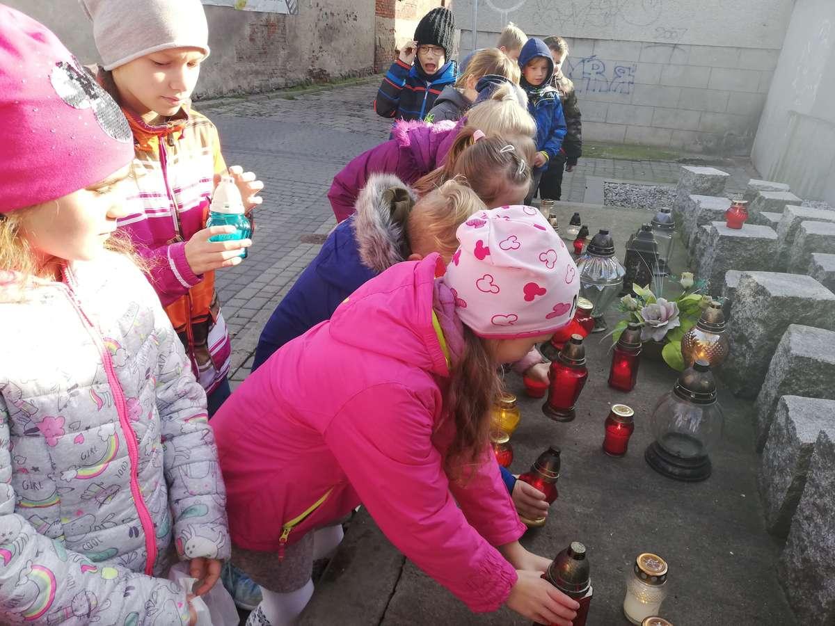 Uczniowie przy pomniku pomordowanych na ul. 7 Grudnia w Nowym Mieście