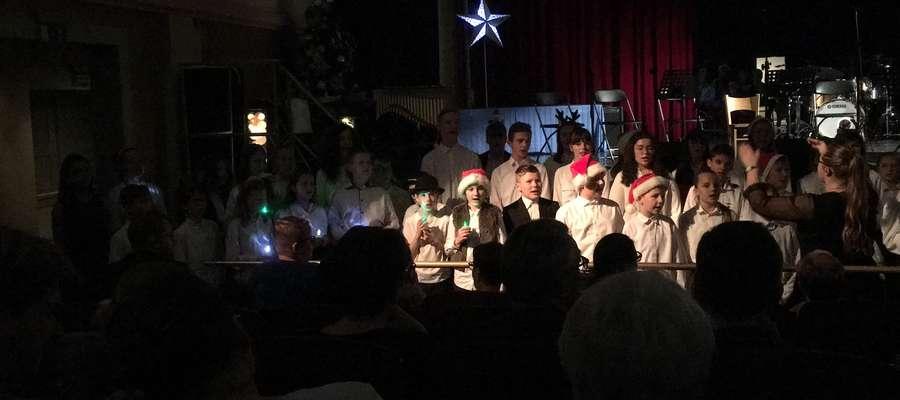 """Wielką atrakcją wieczoru był występ chóru i Zespołu Wokalnego """"Canzonetta"""", które schodząc z góry z dwu stron w kierunku sceny z lampionami (przy wyłączonym oświetleniu sali) zaśpiewały kolędy"""