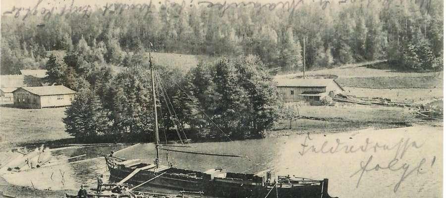 Buńki przed wojną: na pierwszym planie binduga z barką do transportu drewna, po prawej w głębi tartak Luxa, po lewej parterowy drewniany budynek to sala do tańców. Za nim głębi po lewej budynki młyna