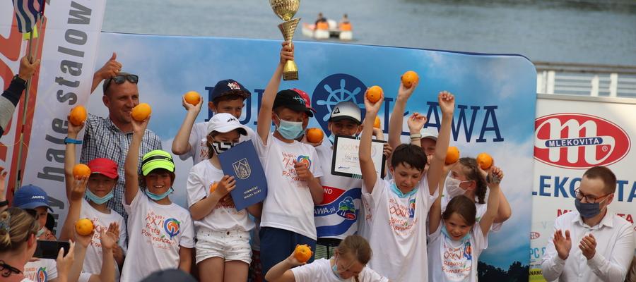 Młodzi żeglarze MOS Iława (wraz z trenerem Michałem Maśkiewiczem) na najwyższym stopniu podium 36. Regat Pomarańczowych, oczywiście z pomarańczami w dłoni