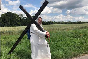 Samotny pielgrzym z krzyżem na ramionach