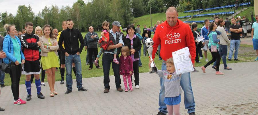 Puchar Burmistrza Bisztynka prezentuje córka kapitana zespołu FC Chlewki, który zwyciężył w X Letnich Rozgrywkach w Piłkę Nożną.