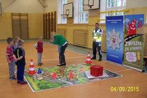 Dzieci uczą się jak bezpiecznie poruszać się po drodze i przechodzić przez pasy
