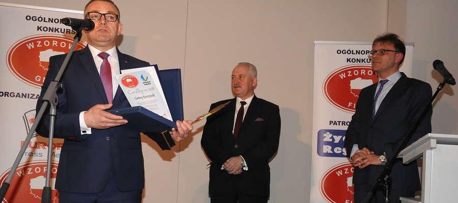 Wójt Wojciech Dereszewski prezentuje wyróżnienie w towarzystwie marszałka Gustawa Marka Brzezina i organizatora przedsięwzięcia Artura Świtona