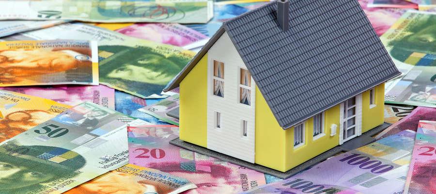 Ilustracja do tematu o kredytach frankowych- model domu stojący na banknotach.