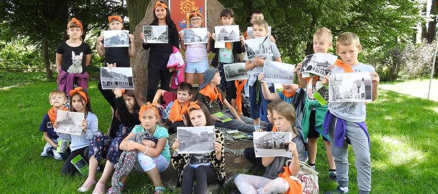Pamiątkowe zdjęcie przy Kamieniu Plebiscytowym. Dzieci trzymają archiwalne zdjęcia Bisztynka pokazujące obiekty, których już nie ma i które dziś zobaczyły.