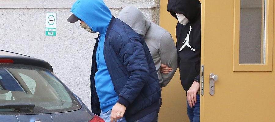 Jeden z byłych policjantów był przesłuchiwany w olsztyńskim sądzie rejonowym. Na zdjęciu: w asyście funkcjonariuszy opuszcza sąd po przesłuchaniu