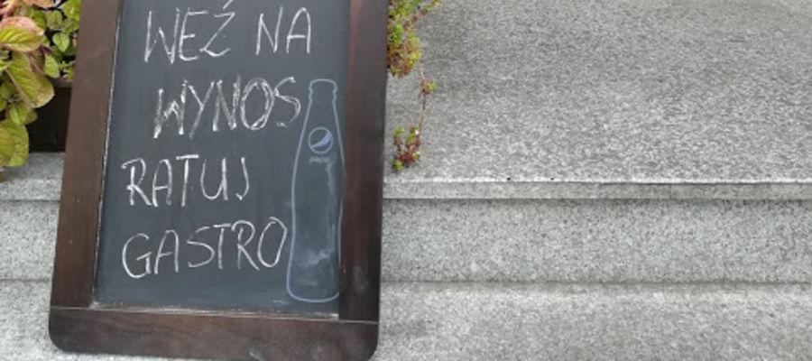 Przed drzwiami lokalu Na Prostej szyld zachęca do ratowania gastronomi zakupami na wynos