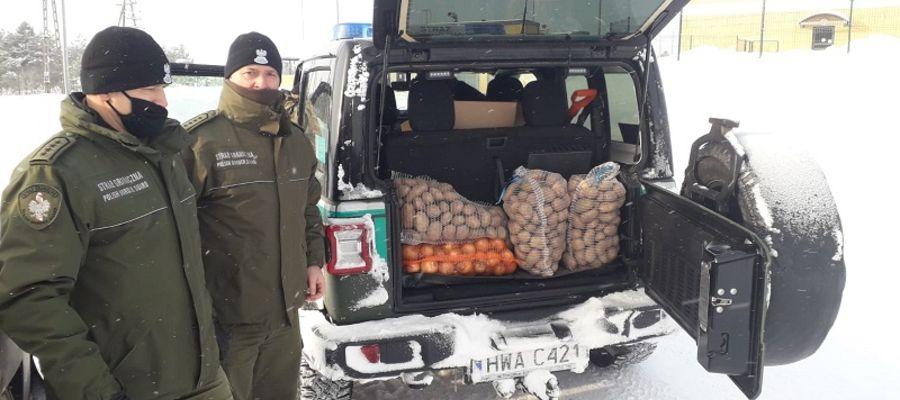 Funckonariusze z Placówki Straży Granicznej w Gołdapi pomagają starszemu małżeństwu z Puszczy Romincjiej.
