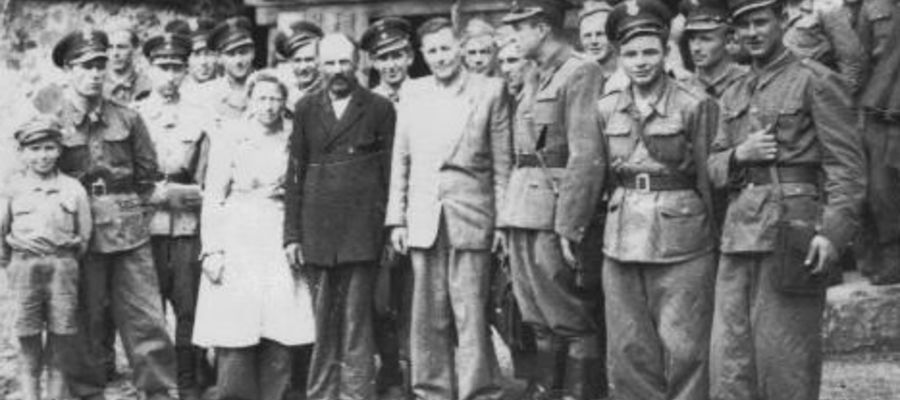 1947 r. Pamiątkowe zdjęcie sołtysa i kierownika szkoły z brygadą żołnierzy pracujących w gospodarstwie rolnym