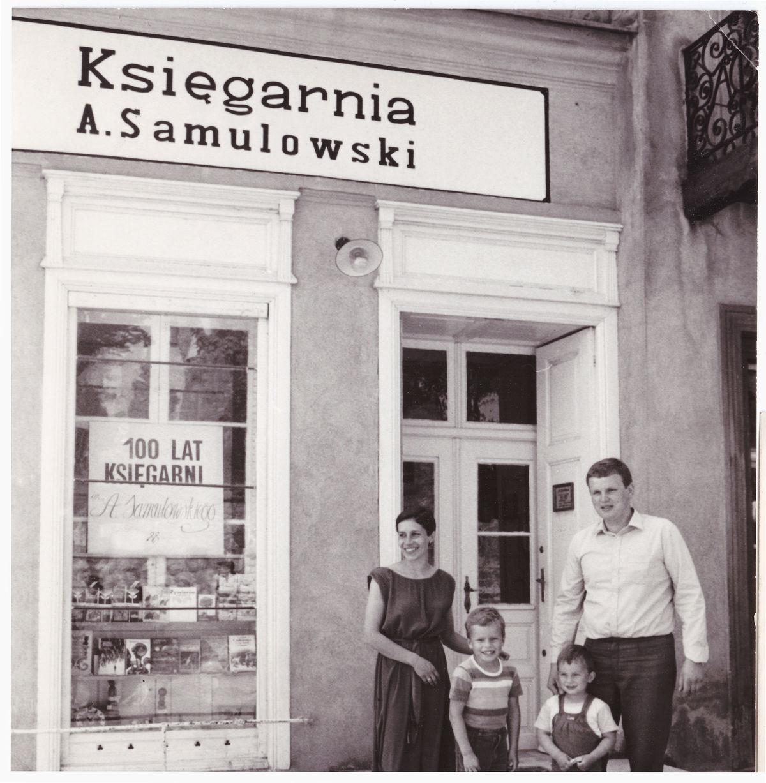Przed księgarnią i domem Samulowskich. Wojciech Samulowski z żoną Teresą i synami Lucjanem i Andrzejem, Gietrzwałd, 1985 rok