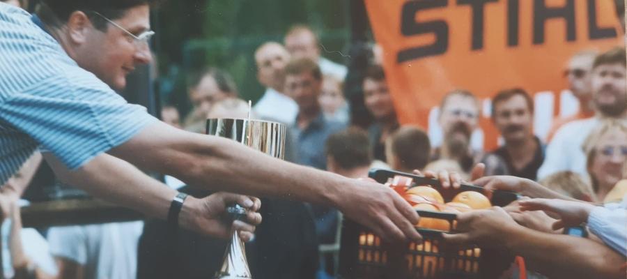 """Zdjęcie """"wykopane"""" z archiwum Gazety Iławskiej. Trener Marek Karbowski (MOS SSW Iława), jakieś 15 lat temu podczas Regat Pomarańczowych, podaje słynną już skrzynkę pomarańczy, która jest główną nagrodą dla zwycięzcy w klasyfikacji klubowej"""