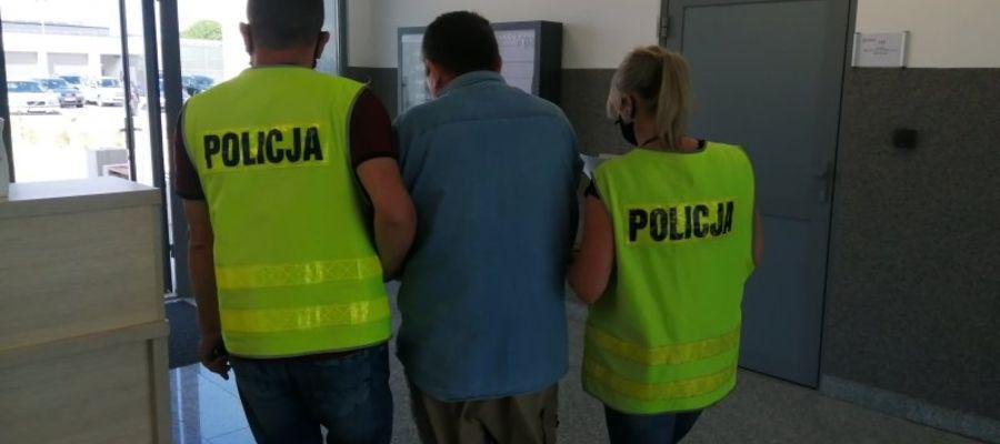 policjanci w trakcie doprowadzenia 60 - latka do prokuratury