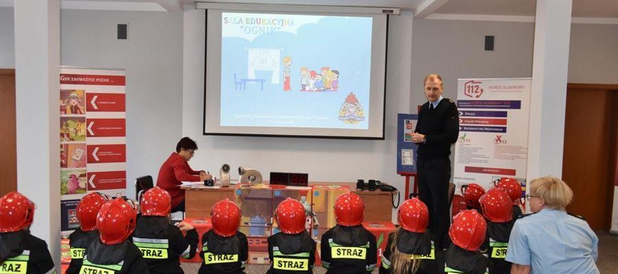 """Dzieci siedzą i wysłuchują prelekcji w sali edukacyjnej """"Ognik"""""""