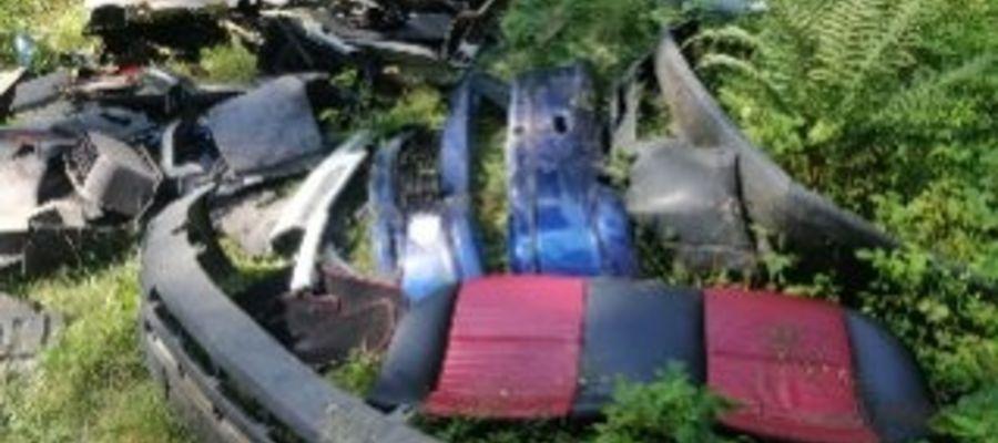Części z rozbiórki samochodu wyrzucone do lasu